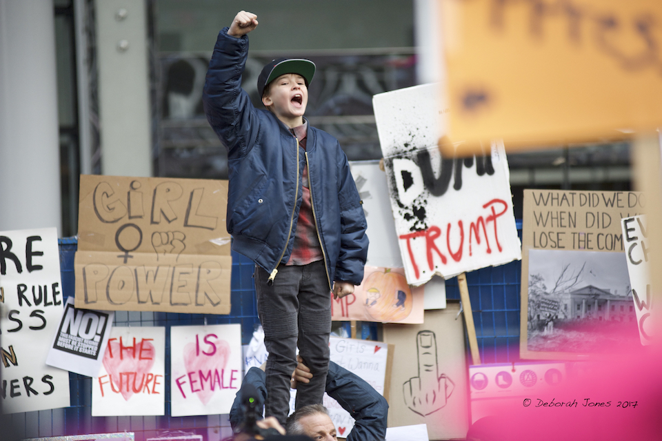 A boy standing on a man's shoulders outside the Trump Tower, Vancouver, Canada, leads a chant at the Vancouver Women's March on January 21, 2017, to protest Donald Trump's inauguration. Photo Deborah Jones © 2017
