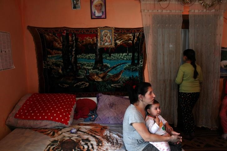 A mother holds her baby during a home visit from doctor Robert Ganea (not in the picture) in the village of Sacel in Romania, January 4, 2017. REUTERS/Andreea Campeanu