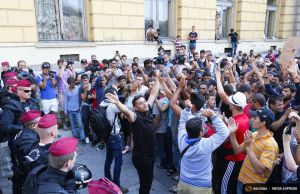 Hungarian police officers face migrants outside the Eastern railway station in Budapest