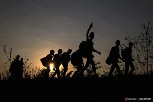 Migrants, hoping to cross into Hungary, walk along a railway track outside the village of Horgos in Serbia, towards the border it shares with Hungary