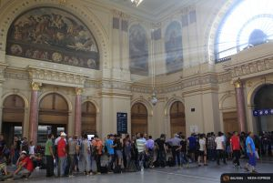 People stand in a queue to buy train tickets a the railway station in Budapest