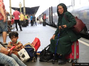 Travellers sit on a platform as they wait for a train to Austria at the railway station in Budapest