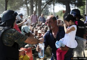 A policeman assists a family as migrants try to enter Macedonia near Gevgelija near the border with Greece