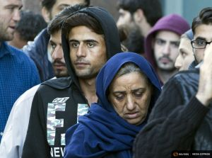 Migrants seeking asylum status queue outside the foreign office in Brussels