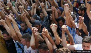 Syrian refugees raise their arms in front of the railways station of Budapest