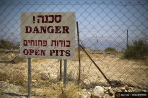 A sign warning of sinkholes is seen on a fence on the shore of the Dead Sea near Ein Gedi