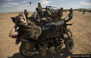 Enthusiast Deegan waits on his motorcycle during Wasteland Weekend event in California City