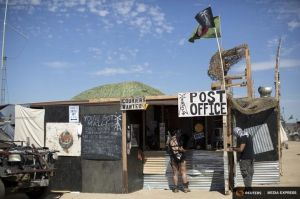 People stand at a post office during Wasteland Weekend event in California City