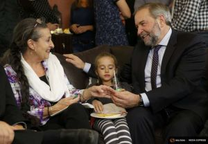 Canada's New Democratic Party leader Tom Mulcair sits with family members as he watches election results at a hotel in Montreal
