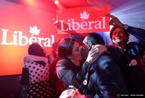 Liberal Party supporters kiss as they celebrate while watching results during Canada's federal election in Montreal