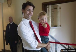 Liberal leader Trudeau carries his son Hadrien as he enters the polling station to cast his vote in Montreal