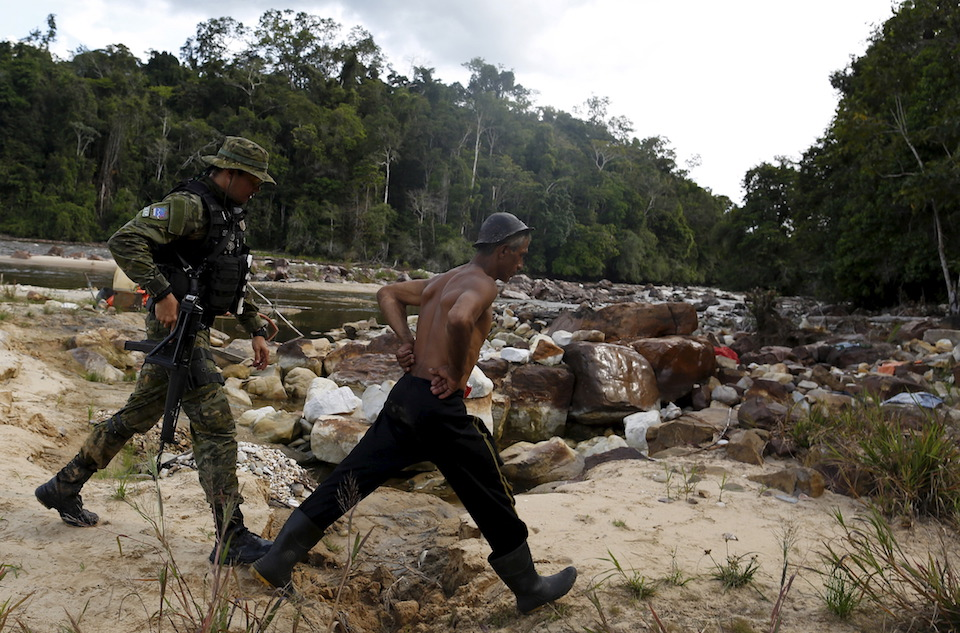 "An agent of Brazil's environmental agency detains a man at an illegal gold mine during an operation against illegal gold mining on indigenous land, in the heart of the Amazon rainforest, in Roraima state, Brazil April 18, 2016. At over 9.5 million hectares, the Yanomami territory is twice the size of Switzerland and home to around 27,000 indians. The land has legally belonged to the Yanomami since 1992, but illegal miners continue to plague the area, sawing down trees and poisoning rivers with mercury in their lust for gold. REUTERS/Bruno Kelly SEARCH ""AMAZON GOLD"" FOR THIS STORY. SEARCH ""THE WIDER IMAGE"" FOR ALL STORIES"