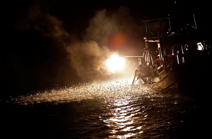 """Fishermen light a fire to attract fish on a traditional """"sulfuric fire fishing"""" boat in New Taipei City, Taiwan June 19, 2016. REUTERS/Tyrone Siu"""